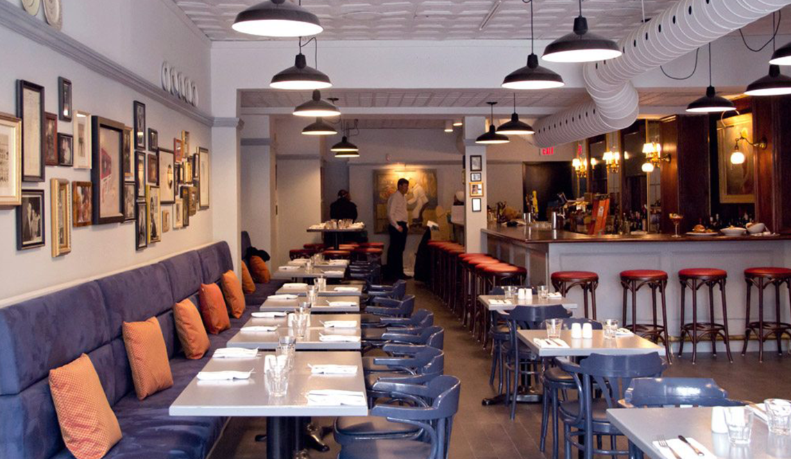 Interior of Brooklyn Tavern in Leslieville, Toronto. A row of banquet seats with all tables set. A bar is in the background on the right hand side. Warm lighting and a tin ceiling.