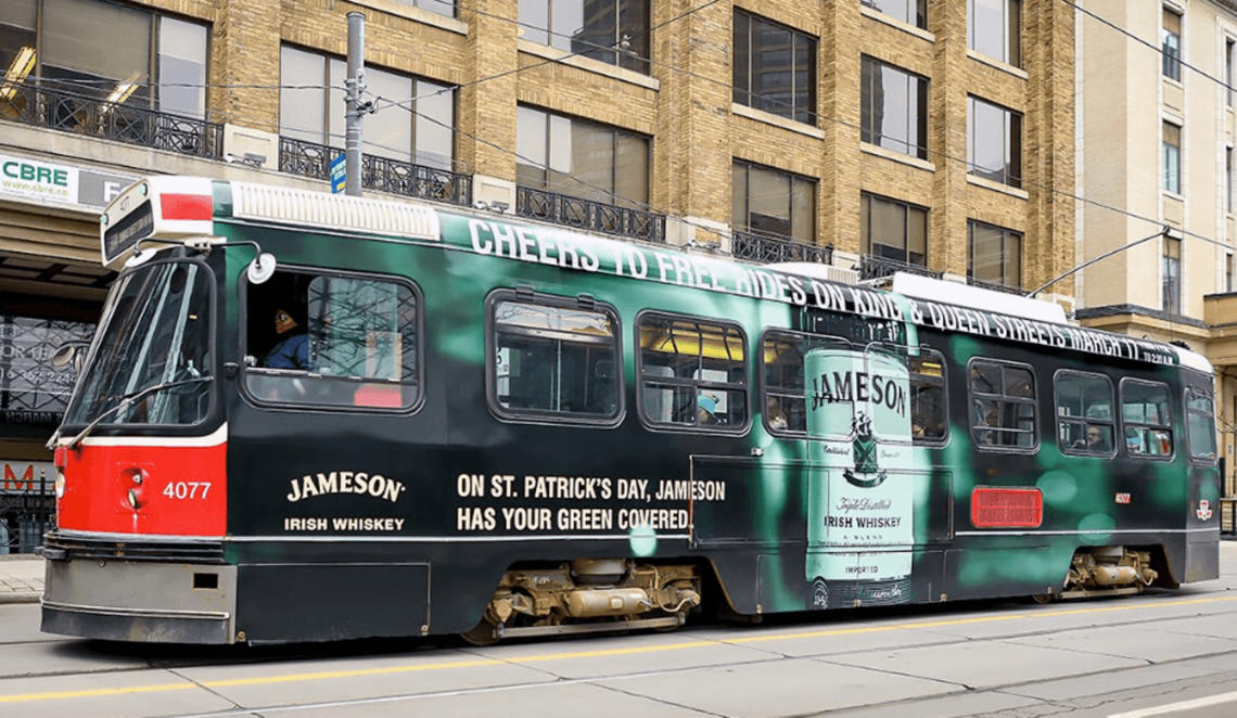 TTC Streetcar wrapped in a green Jameson advertisement stating: TTC Streetcars are free along King and Queen on St. Patrick's Day in Toronto